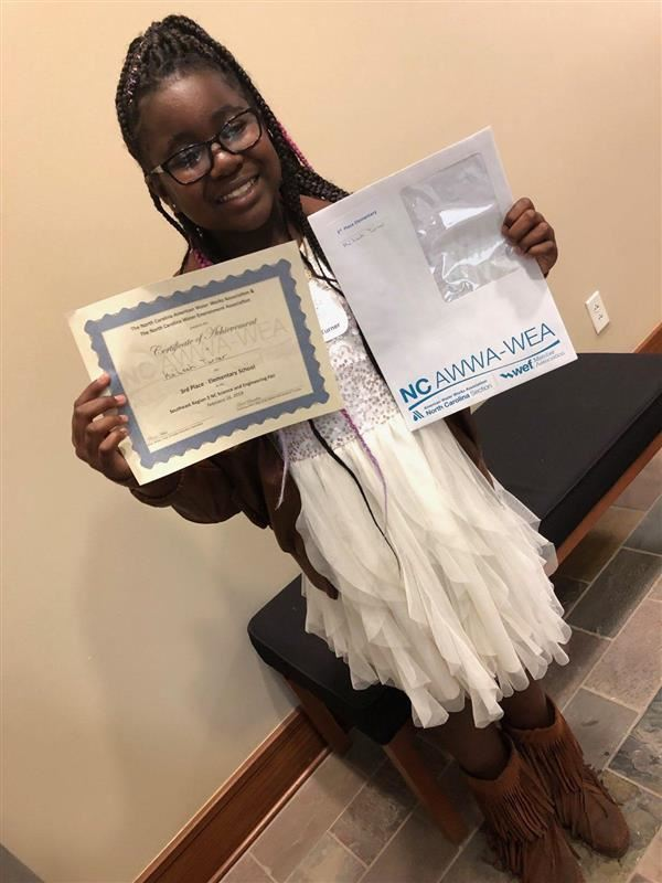 Picture of student with award certificate