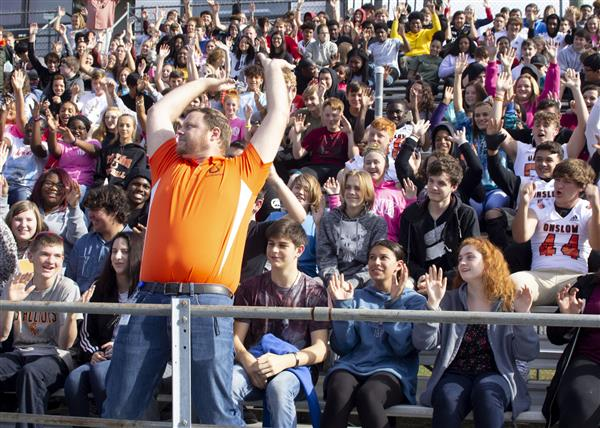 Carl Cruthis leads students in a roller coaster cheer