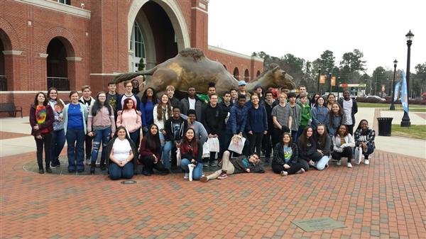 students posing around the Campbell Camel