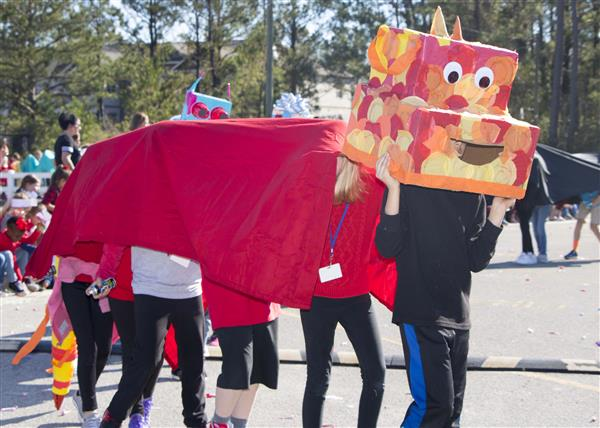 Children at Dixon Elementary wear the dragon they made for their Chinese New Year parade
